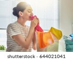 Stock photo beautiful young woman is smelling clean clothes and smiling while doing laundry at home 644021041