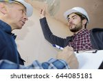 apprentice pointing at the ceiling - stock photo