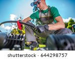 Building Garden Watering System. Professional Watering Systems Technician Cutting Plastic Water Supply Pipe. - stock photo