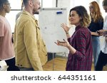 Small photo of Cheerful male and female colleagues having fun joking while resting after working session on break in coworking space, hipster girl communicating with friends telling interesting stories in good mood