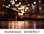 Stock photo wood table top with reflect on blur of lighting in night cafe restaurant background selective focus 644369617