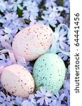 Three beautifully decorated Easter eggs lying in a bed of phlox. Shallow DOF with selective focus on eggs. - stock photo