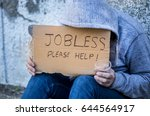 Small photo of Jobless man begging on a street holding a handwritten sign for help covering his face as he sits on the sidewalk in jeans and a hoodie holding a cup for coins