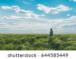 Farmer Walking Through A Green...