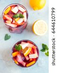 Small photo of Red wine sangria or punch with fruits, mint and ice in glasses. Homemade refreshing fruit sangria over rustic white table, copy space