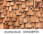 Small photo of Unregular pattern of overlapping Western Red Cedar shingles natural organic wooden wall siding for residential buildings