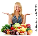 Young blond woman standing at the table with variety of fresh raw vegetables - stock photo