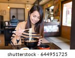 young woman eating japanese... | Shutterstock . vector #644951725