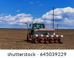 Small photo of A beautiful landscape close up of a tractor with a seeder during planting the field. Fluffy clouds in the sky, a slight defocus with front bokeh. Concept agro culture.