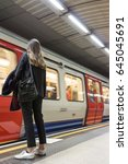 Small photo of LONDON, UK - 11 MAY 2017: Woman waits to board a speeding moron blurred London Underground tube train