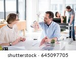 Small photo of Happy director is holding tablet and gesturing. He sitting afore female coworker, who listening attentively. They are working together in office