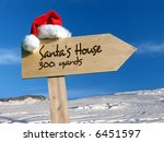 Wooden signpost with Santa's hat indicating Santa's House with snow and blue sky in the background - stock photo