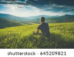tourist sitting on a hill in a... | Shutterstock . vector #645209821