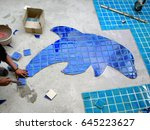 Tiled pool. The man hand while using spacer for installing tiles. construction work.Construction Pool.Technicians are tiled swimming pool. - stock photo