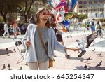 laughing woman feeding pigeons... | Shutterstock . vector #645254347