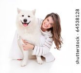 Stock photo a studio image of a young woman dressed in white with her white dog huging it both posing 64538128