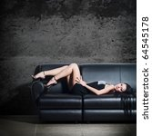 The beautiful woman lying on a leather sofa - stock photo
