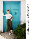 Small photo of Beautiful petite brunette lady in ethnic national boho styled clothes poses next to vintage antique turquoise door in small medieval village during summer breakaway to find peace and tranquility