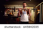 Small photo of Man athlete with the barbell at the gym
