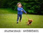Stock photo lillte girl running outside with her cute dog cavalier king charles spaniel puppy 645885601