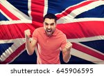 Small photo of emotion, aggression, patriotism, gesture and people concept - angry young man showing fists and shouting over brittish flag