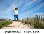 happy middle aged woman jumping ... | Shutterstock . vector #645935545
