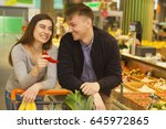 Small photo of Beautiful woman holding red chili pepper smiling at her boyfriend seductively while shopping together at the local supermarket copyspace attraction passion seduction spicy love flirting aphrodisiac