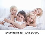 a happy family on white bed in... | Shutterstock . vector #64610497
