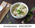 Shrimp wonton with braised pork in soup on wooden table / Select focus image