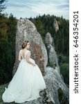 Small photo of Beautiful bride stands straight against the wind on the rock