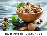 mixed nuts in a wooden bowl on... | Shutterstock . vector #646574731
