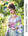 Small photo of Spring Beautiful romantic girl with perfect hairstyle standing on green backround with cup of tea. Dreaming princess in fairy beautiful vintage dress between flying seeds of dandelions looking afar