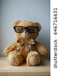 Small photo of Smiling and smug teddy bear in glasses