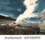 Small photo of The eagle flies through the ejection of steam from the geyser. Valley of Geysers in the Atacama Desert, Chile