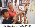 teacher assisting schoolboy in... | Shutterstock . vector #647455945