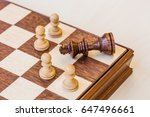 Small photo of chess game. abstract composition of chess figures in chessboard isolated on light background. black king surrounded white pawns. utter defeat.