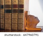Small photo of Old Bind Books held by a glass art deco woman's head book holder.