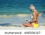 Young Woman In Bikini Reading A ...