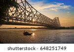 Stock photo wooden boat passing the historic howrah bridge in silhouette at sunrise howrah bridge is a 648251749