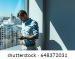 young businessman looking at... | Shutterstock . vector #648372031