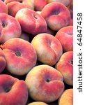 Flat peaches, called paraguayas in a market stall - stock photo