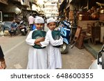Small photo of Mumbai, India - October 11, 2015: Two Muslim boys of Dawoodi Bohra sect wearing traditional dresses going to religious school at local mosque during Ramadan holy month at Chor Bazaar thief market