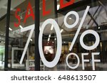 Small photo of Large Sale 70% off letters on a glass wall obstruct a view inside the popular clothing store