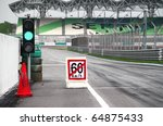 Small photo of Pit stop exit with speed limit signboard and traffic light. Concept of safety measures for motor sport participants.