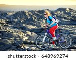 young tourist cycling on lava... | Shutterstock . vector #648969274