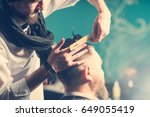 the barber cuts hair  bearded... | Shutterstock . vector #649055419