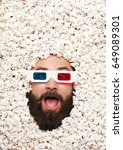 Small photo of Young bearded man looking amazed while wearing 3-D glasses and lying in popcorn.