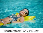 a woman in the pool floats on a ... | Shutterstock . vector #649143229