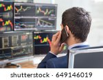 Small photo of Over the shoulder view of and stock broker trading online while accepting orders by phone. Multiple computer screens ful of charts and data analyses in background.