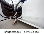 Small photo of woman legs in high heels at the car